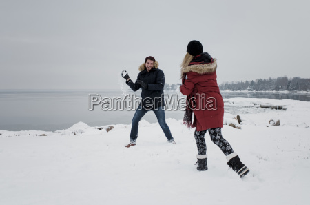 friends playing with snow at beach