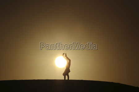 silhouette man doing handstand on field