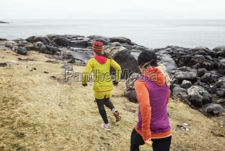 friends running on field by shore