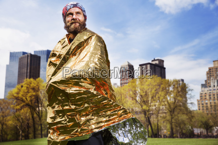 smiling thoughtful man wrapped in golden
