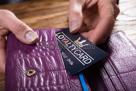 businessperson removing loyalty card from purse