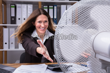 happy businesswoman cooling herself with electrical