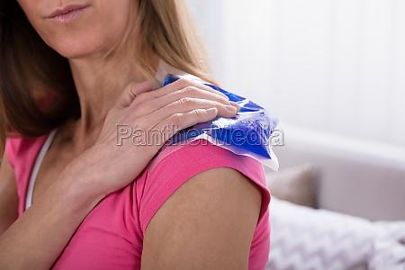 woman applying ice bag on her