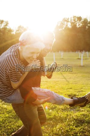 happy man piggybacking friend on playing