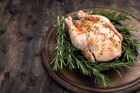 whole raw chicken on wooden cutting