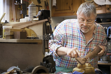concentrated man shaping fretboard in workshop