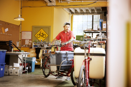 man with container on bicycle at