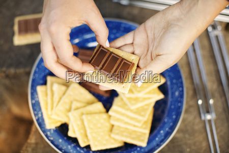 cropped image of hands preparing smores