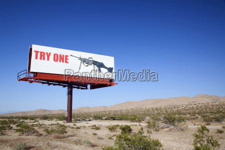 large board advertising machine gun in