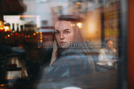 beautiful young woman seen through cafe