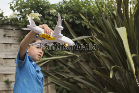 boy playing with toy airplane against