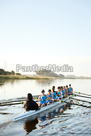 female rowers rowing scull on sunny