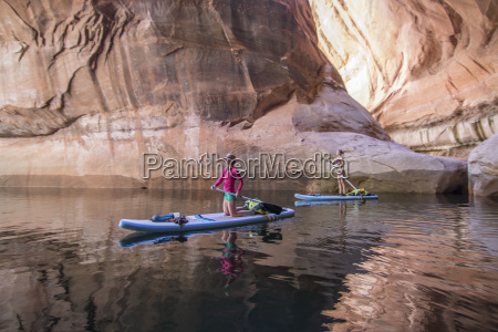 two women paddleboarding through cathedral in