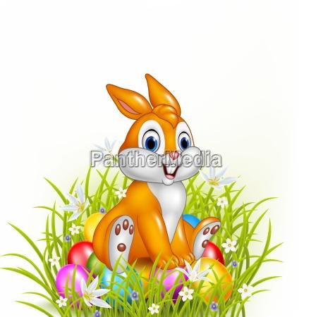 cartoon rabbit sitting on easter eggs