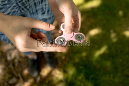 girl playing with fidget spinner