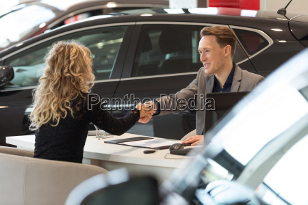 smiling salesman doing handshake with female