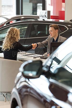 salesman doing handshake with female customer
