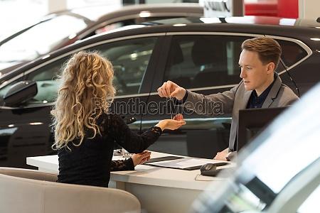 salesman giving keys to female customer