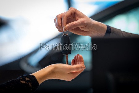 cropped image of salesman giving car