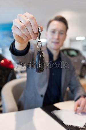 salesman showing car key while sitting