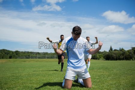 excited football players celebrating after scoring