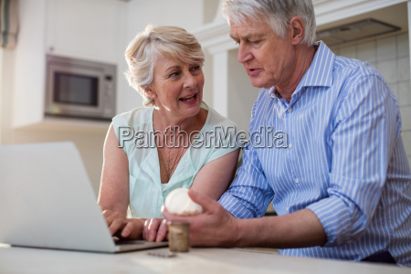 senior couple checking medicine on laptop