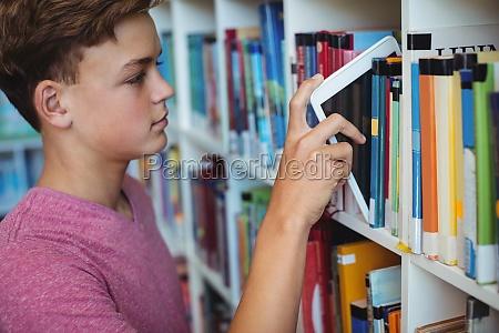 student keeping digital tablet in bookshelf