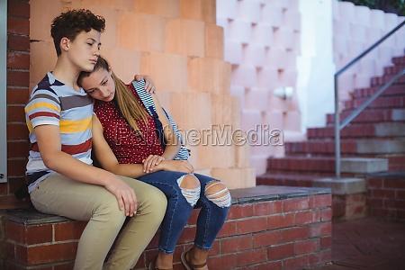 upset school couple sitting near the