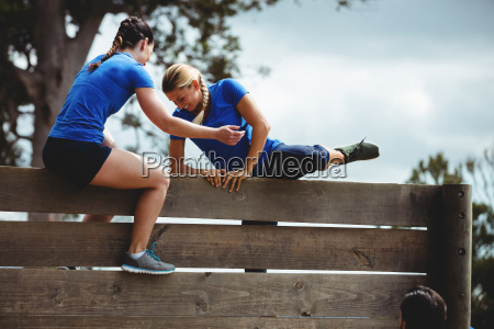 female trainer assisting woman to climb
