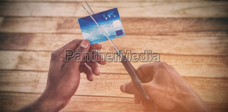 businessman cutting credit card with scissors