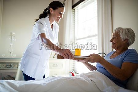 female doctor serving breakfast to senior