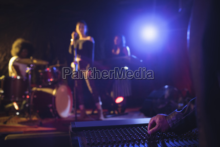 musicians operating sound mixer with performers