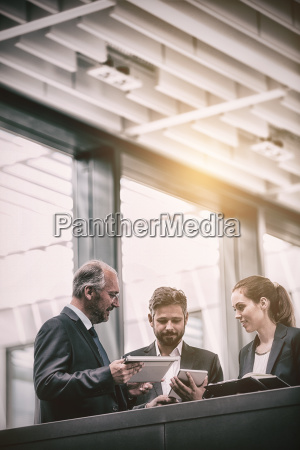 businesspeople discussing over digital tablet