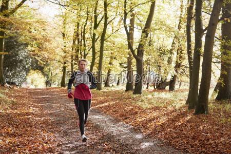 mature woman running through autumn woodland