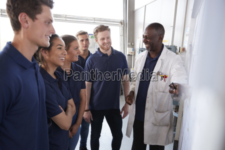 smiling engineering apprentices gather round whiteboard
