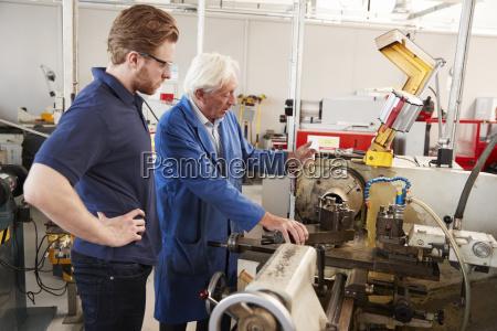 senior engineer instructing apprentice at machine