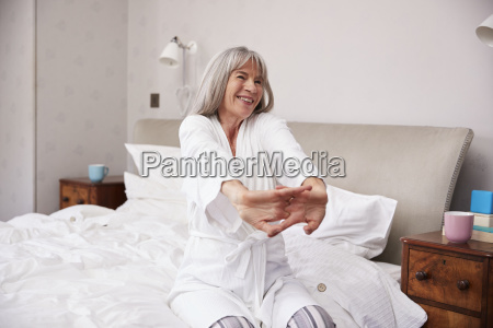 senior woman waking up and stretching