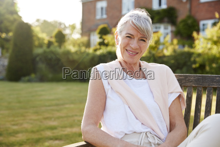 senior woman sitting on garden bench