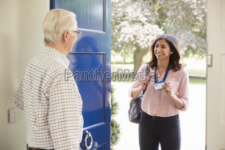 senior man opens front door to