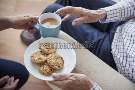 woman passes tea and biscuits to