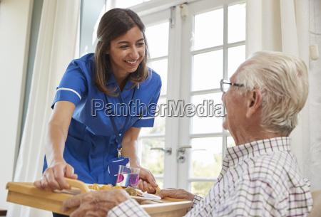 nurse serving dinner to a senior