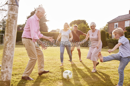 multi generation family playing football in