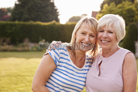 senior woman and adult daughter embracing