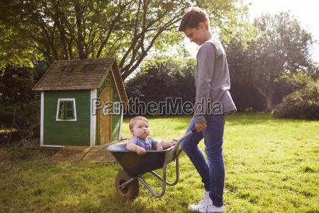 boy pushing baby brother in garden