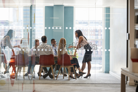 female boss stands leaning on table