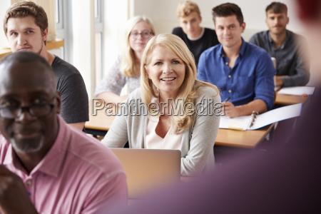 male tutor teaching class of mature