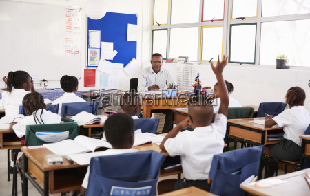 child raising hand to teacher in