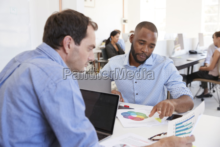 two men discussing documents in a