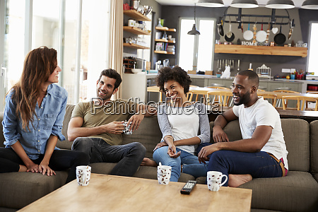 couple sitting on sofa with friends