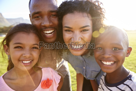 laughing black family outdoors close up